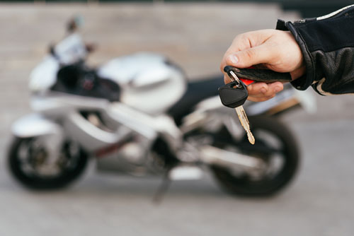 hands holding keys out by a new motorcycle